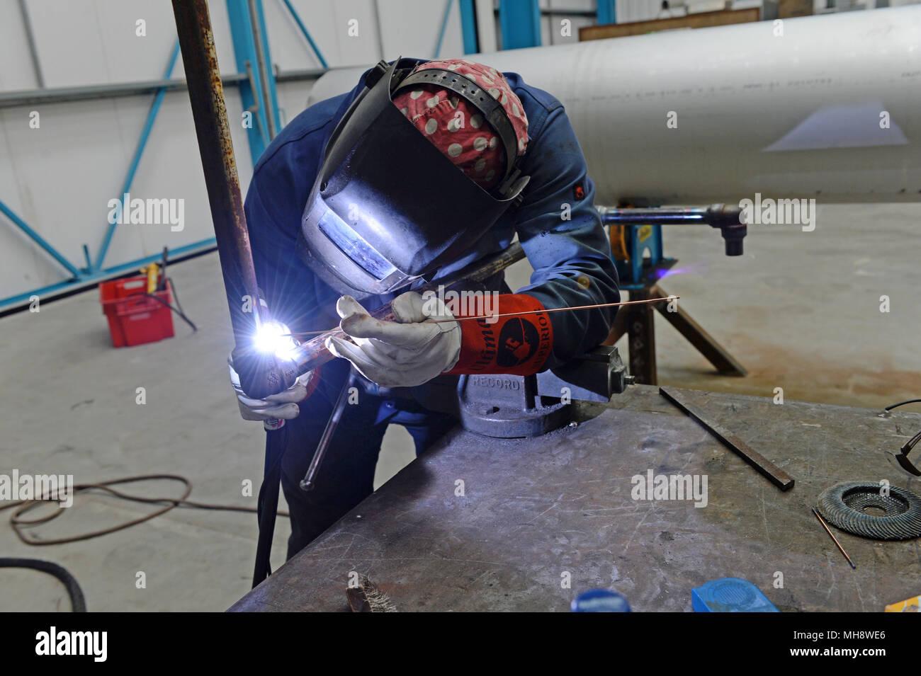 Saldatore saldatura tubo assieme in un laboratorio di fabbricazione Immagini Stock