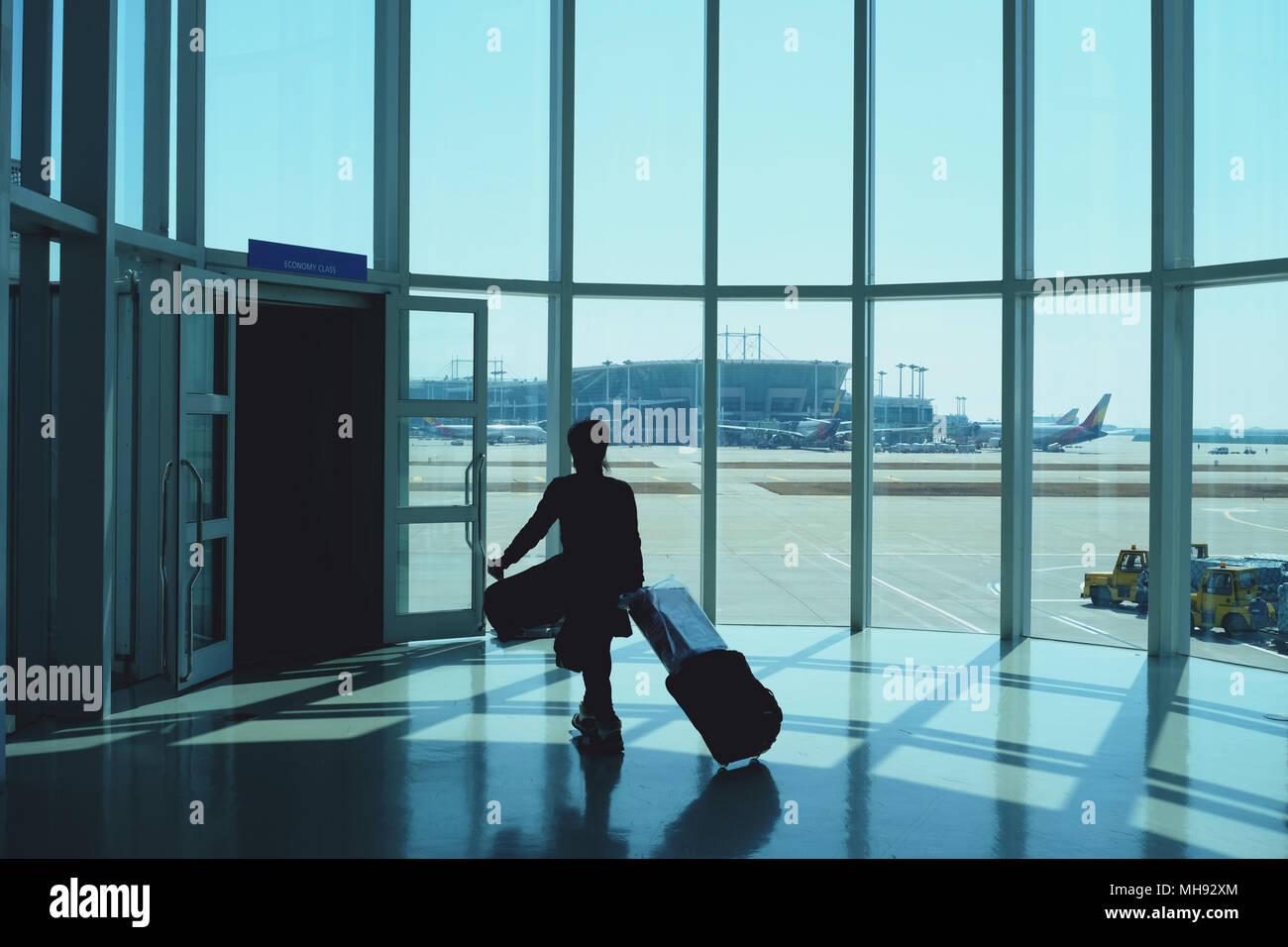 Donna trascinando un piccolo portano sui bagagli in aeroporto il corridoio per raggiungere a piedi i cancelli di partenza silhouette Immagini Stock