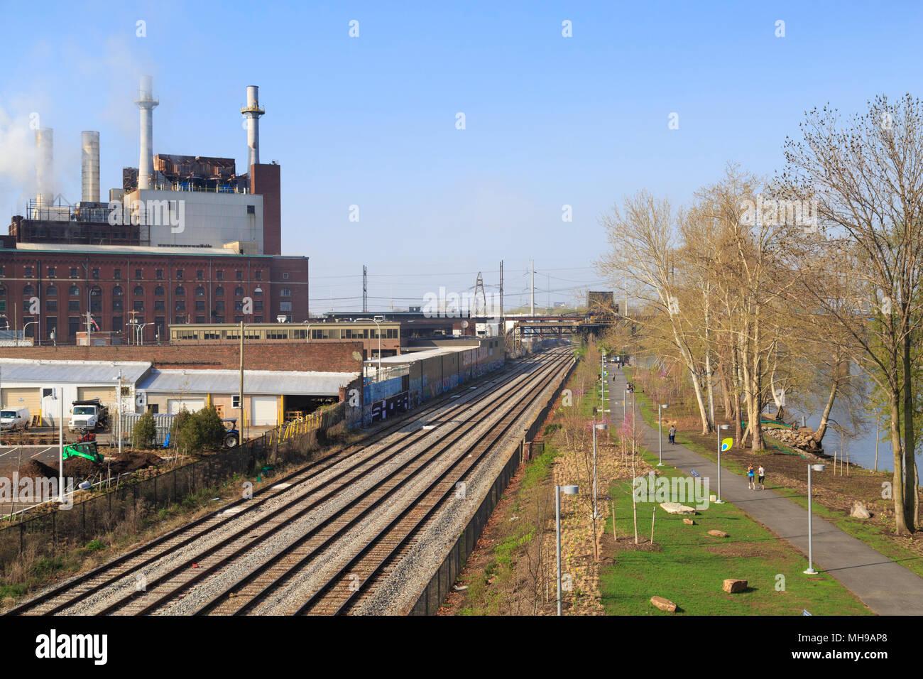 Banche Schuylkill Ricreazione percorso e il treno tracksin rivitalizzato area industriale con Veolia energia termica impianto, Philadelphia, Pennsylvania, STATI UNITI D'AMERICA Immagini Stock