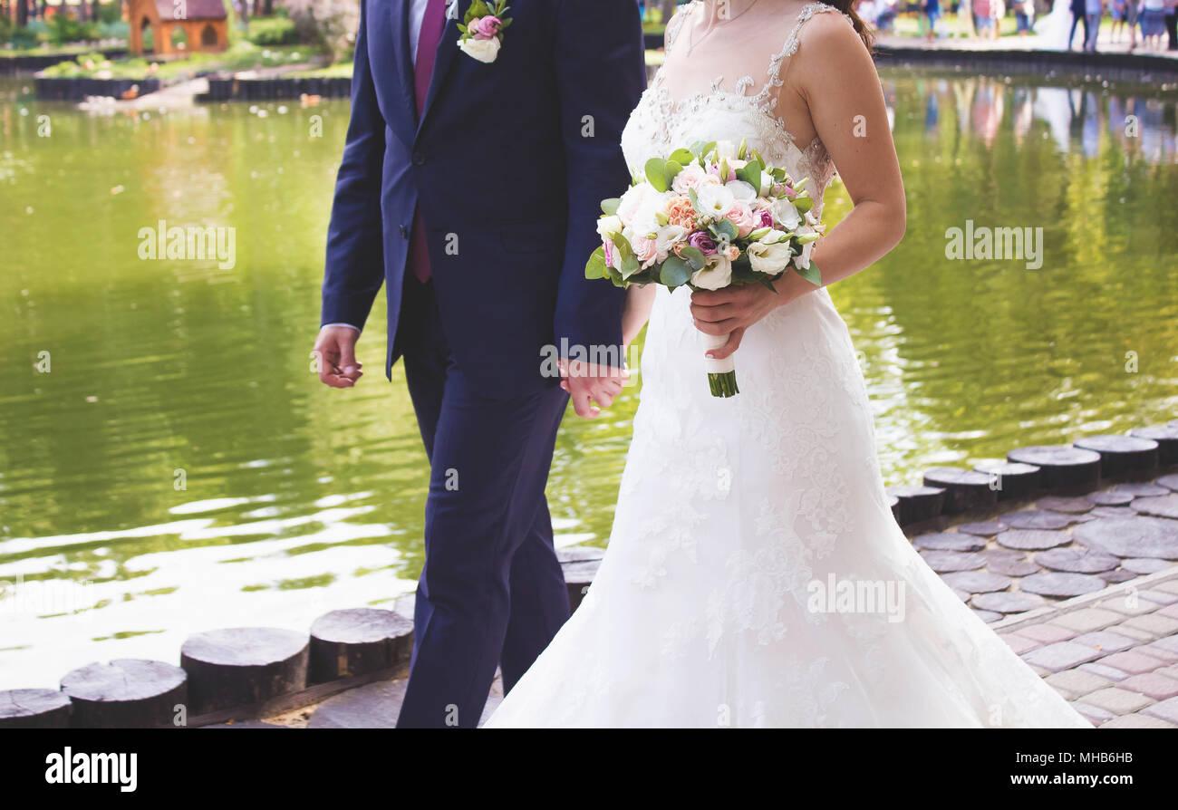 Bouquet nozze da freschi fiori di primavera. Sposa azienda bianco Bouquet nozze close up.Lo sposo tenendo con una mano la sposa in bianco di un abito da sposa Immagini Stock