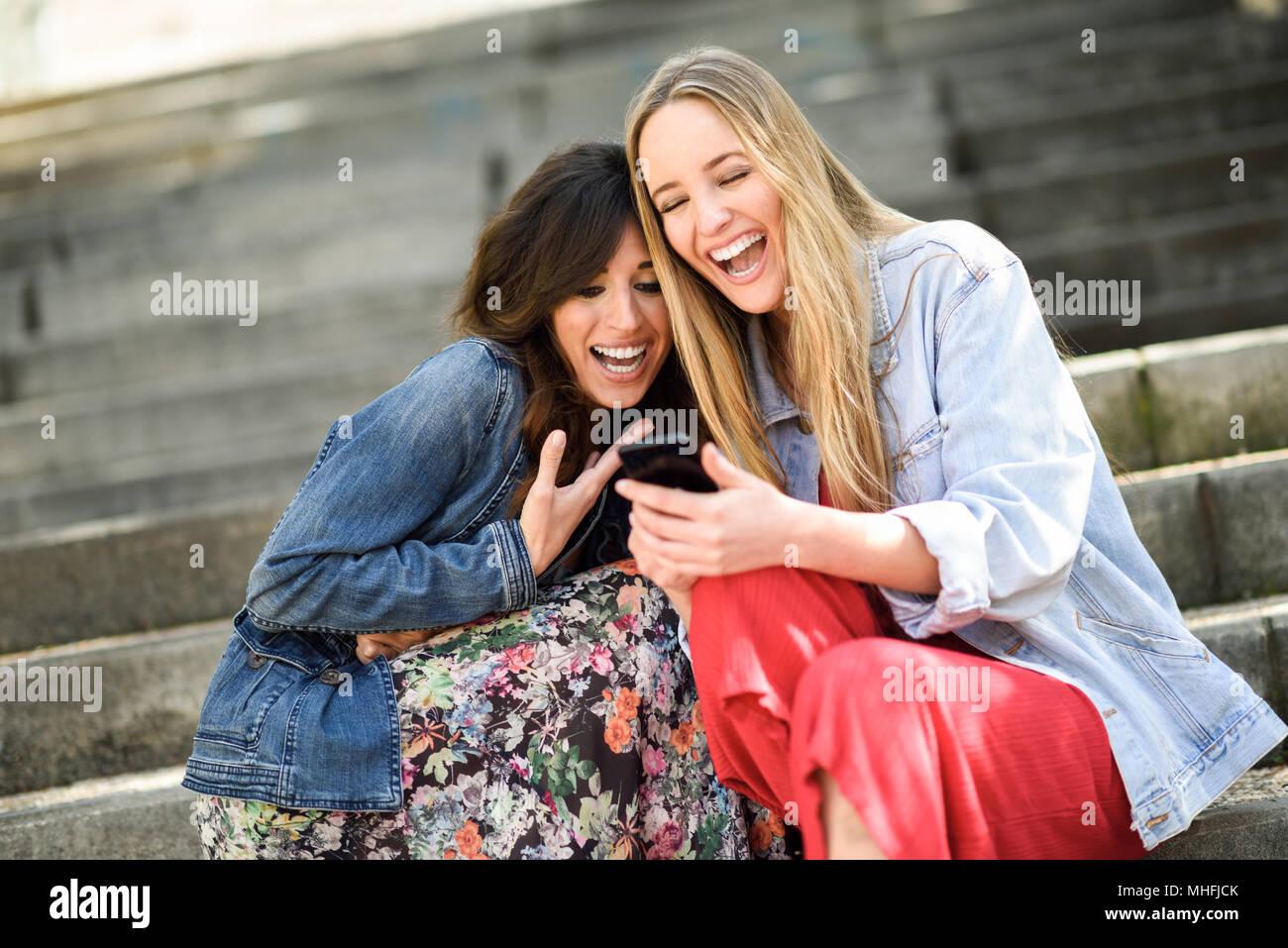 Due ragazze guardando alcune divertenti video su loro smart phone all'aperto, seduti su fasi urbane. Amici di sesso femminile le ragazze a ridere. Immagini Stock