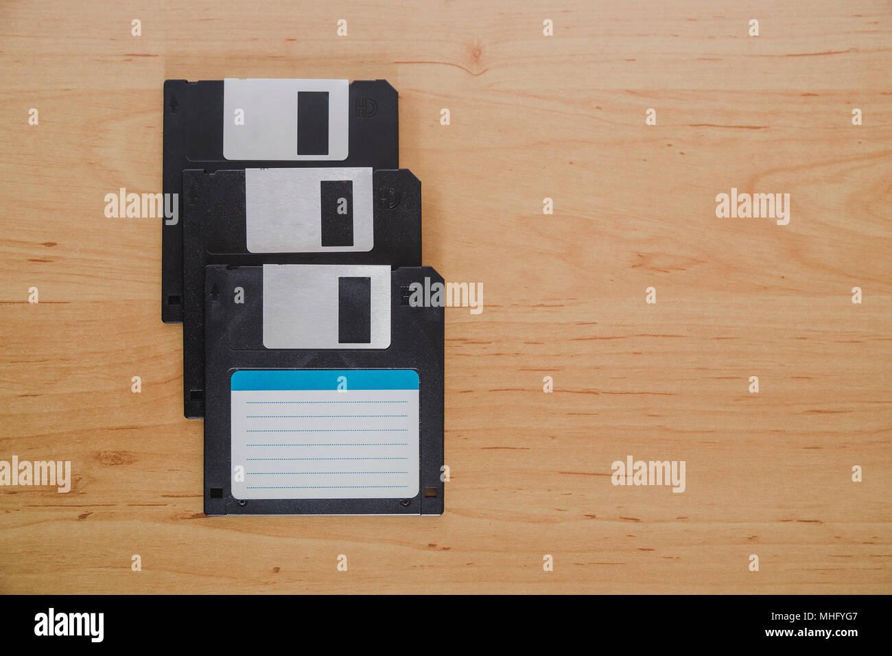 Tre dischi floppy su un sfondo di legno Immagini Stock