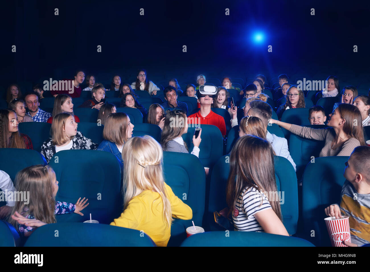 Vista del pubblico la visione di film in movie theater. Ragazzo in bicchieri virtuale seduto in centro. Curiosi che guardano a lui. Proiettore luce sorgente. Concetto di gadget, la cinematografia. Immagini Stock