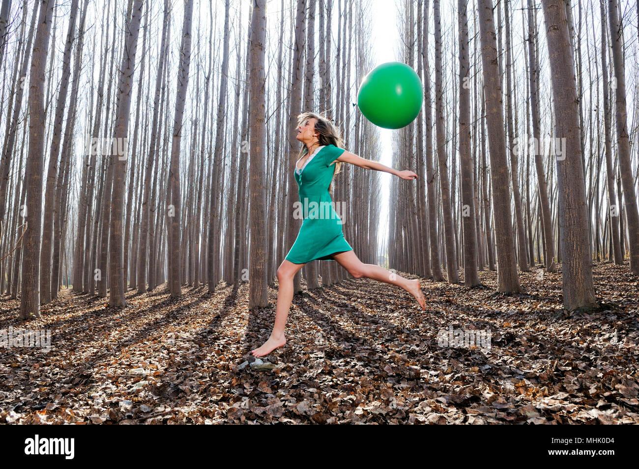 vestito verde ragazza bosco con saltando Bella bionda di un nel qEpIf