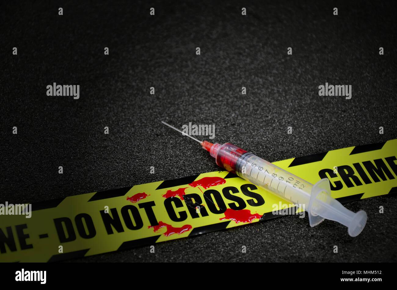 Siringa con non cross della scena del crimine nastro su sfondo scuro Immagini Stock