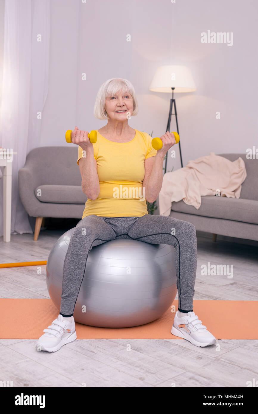 Donna anziana esercizio con manubri su una sfera di fitness Immagini Stock