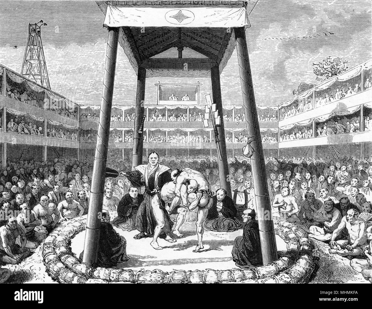 Una masnada di sumo wrestling è guardato da vicino da entrambi gli arbitri e una grande folla. Data: 1865 Immagini Stock