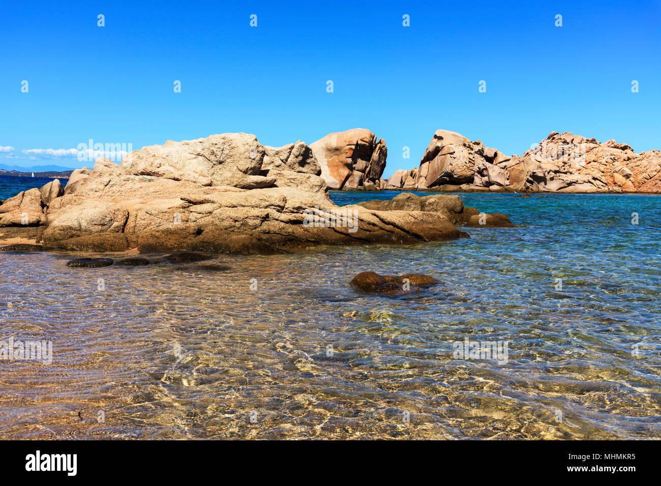 Una vista delle acque limpide del mare Mediterraneo e un gruppo di formazioni rocciose in una tranquilla spiaggia della costa di Baja Sardinia, nella famosa Costa Immagini Stock