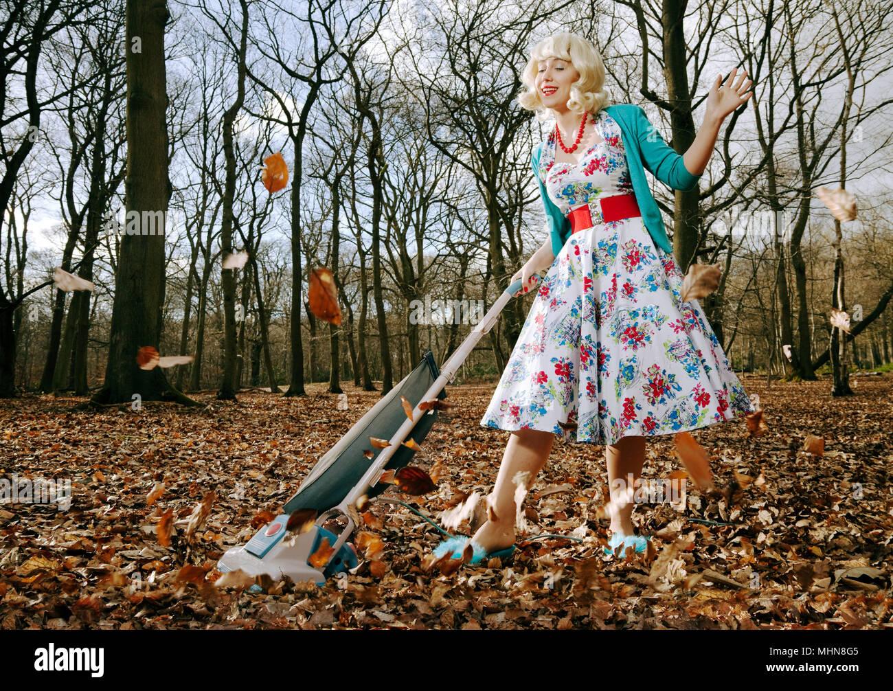 Donna in stile retrò aspirare foglie dei boschi Immagini Stock