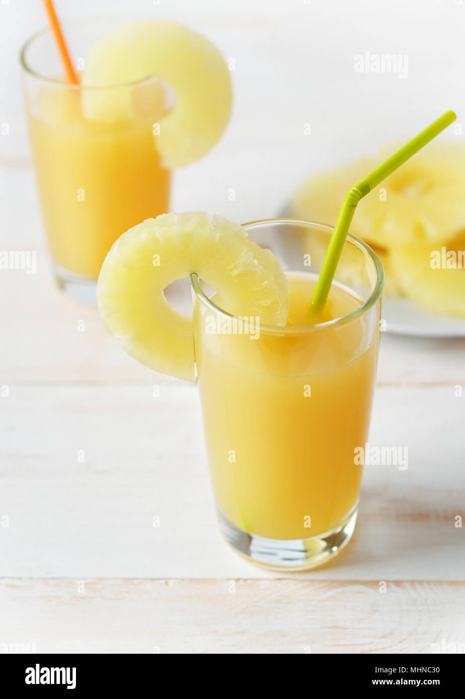 Due bicchieri di succo di ananas su bianco tavolo in legno Immagini Stock