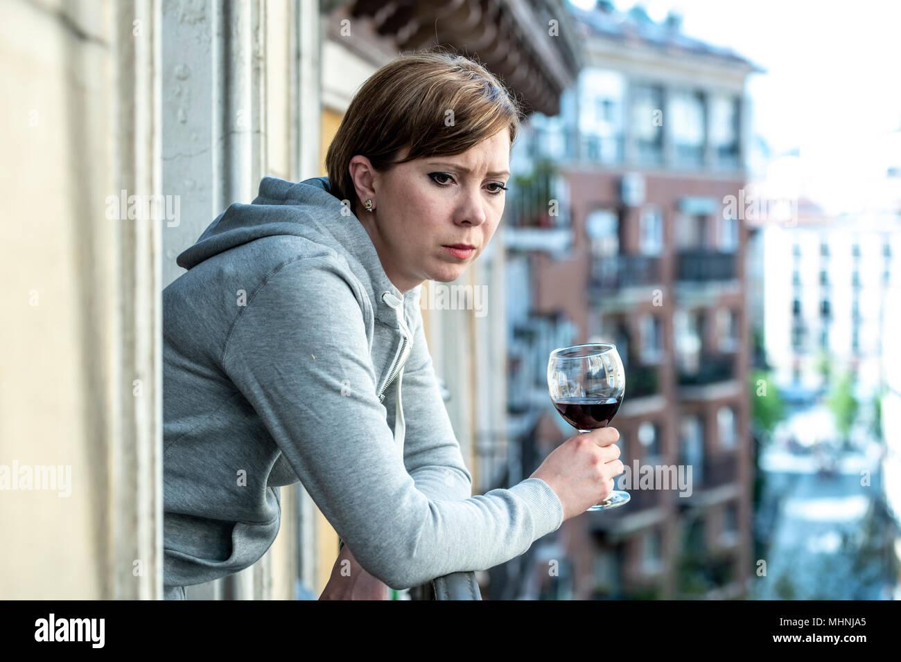 Bella dai capelli rossi donna caucasica affetti da depressione tenendo un bicchiere di vino sul balcone di casa. Guardare fuori sensazione triste, il dolore e il lutto. Immagini Stock