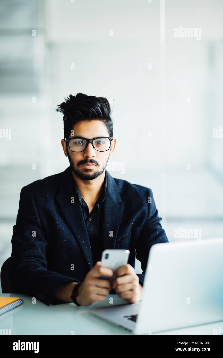 Indian CEO della società nel suo ufficio alla scrivania, la lettura del testo sullo smartphone Immagini Stock
