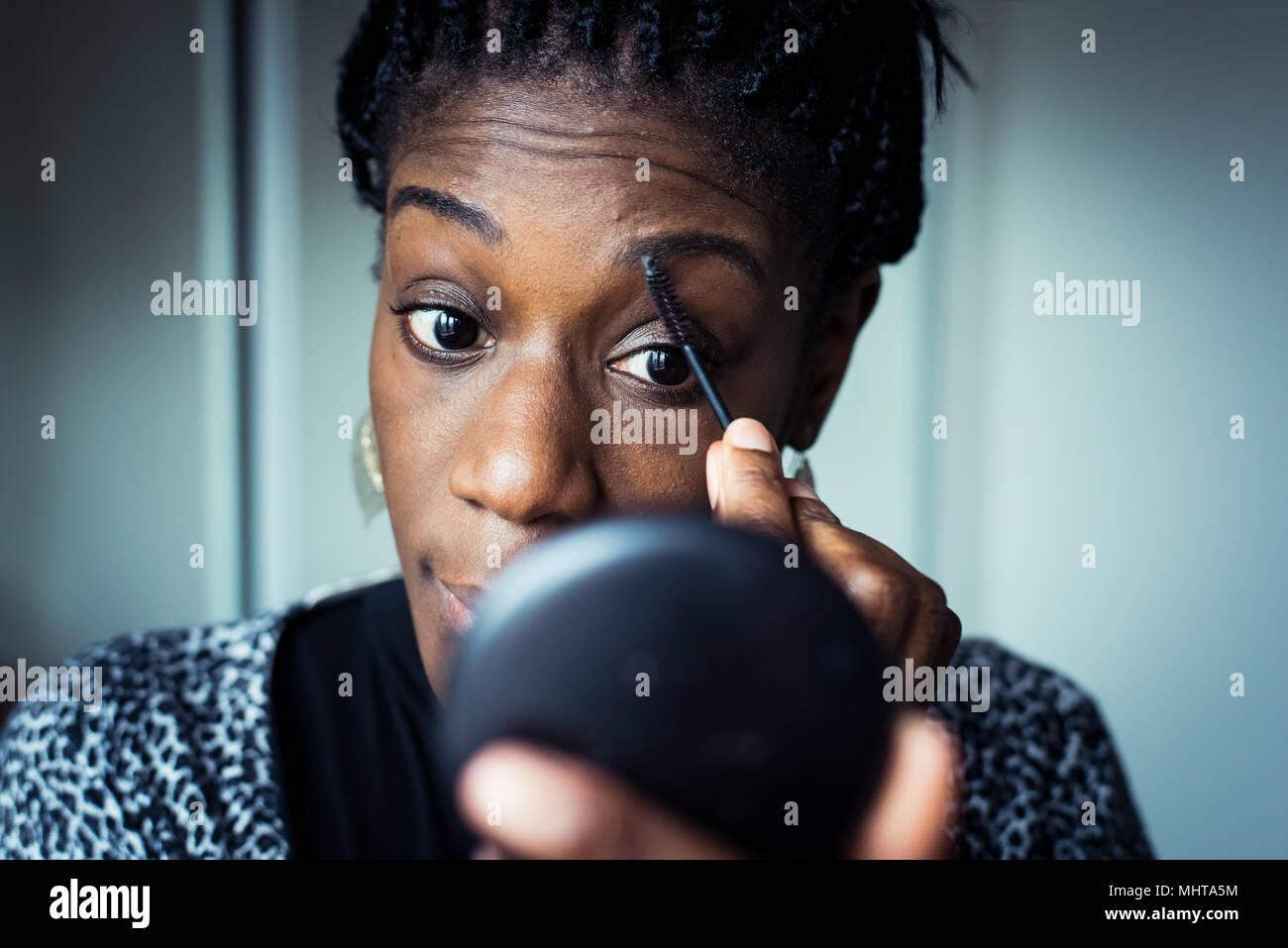 Nero donna preparando per una notte fuori, applicando il trucco in uno specchio a mano Immagini Stock