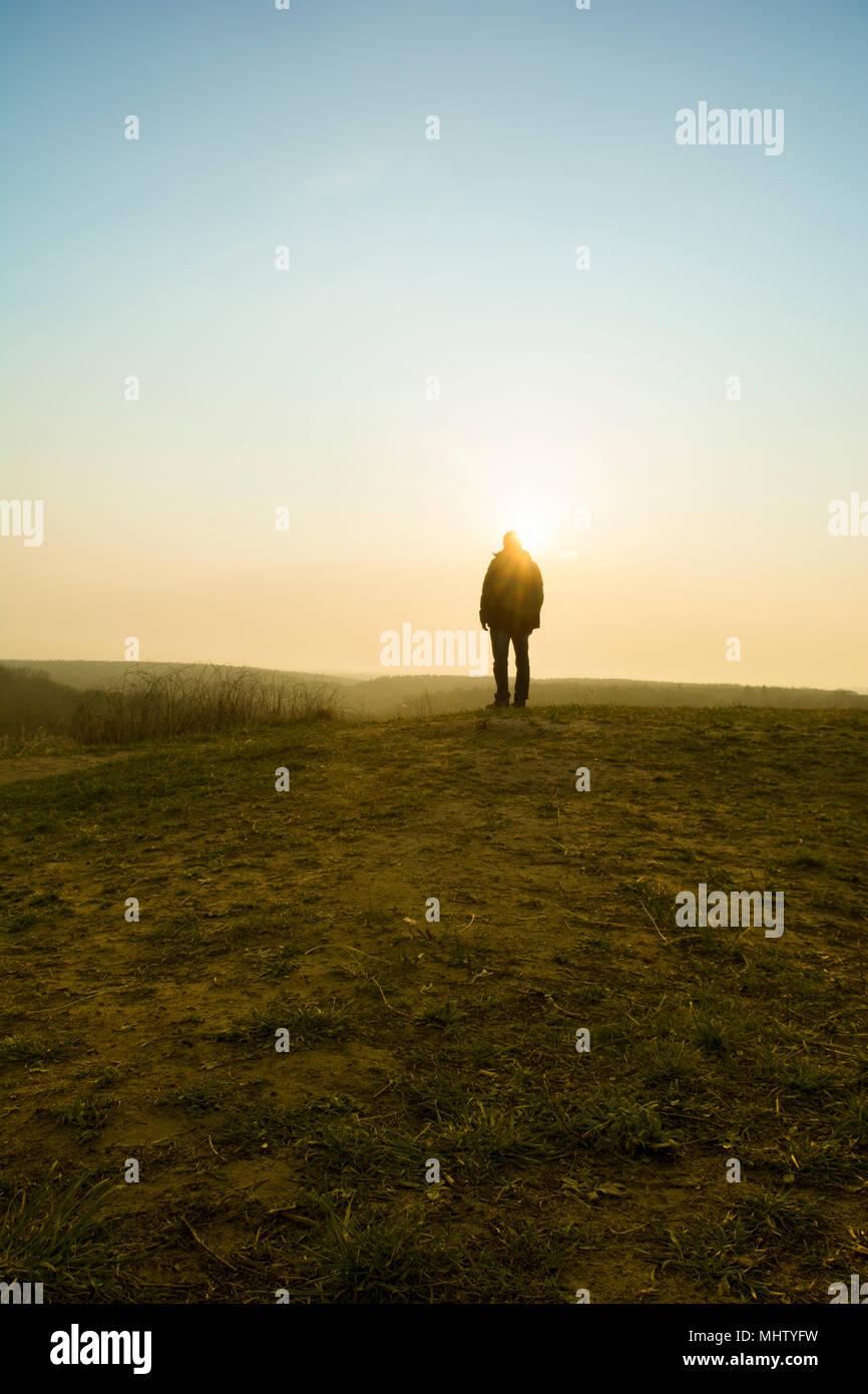 Vista posteriore di una figura maschile in piedi sul campo al tramonto Immagini Stock