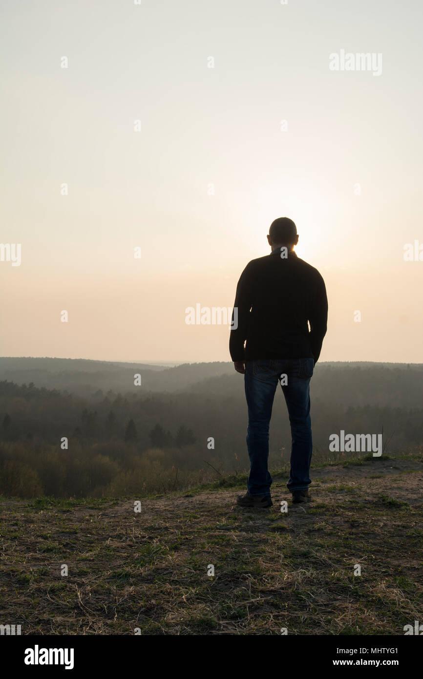 Vista posteriore di un uomo in piedi sulla cima della montagna Immagini Stock