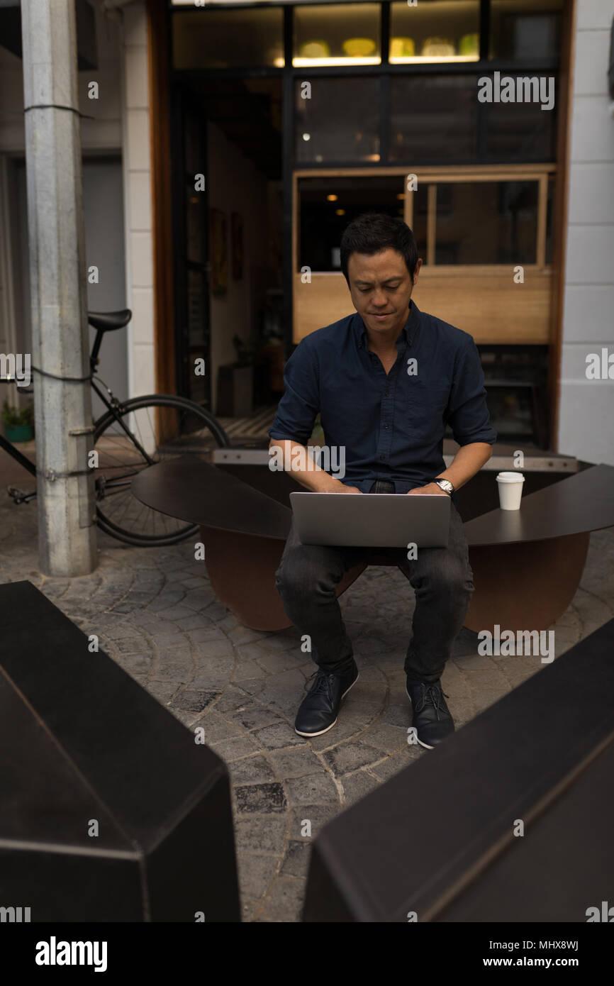 Uomo d affari con computer portatile nel coffee shop Immagini Stock