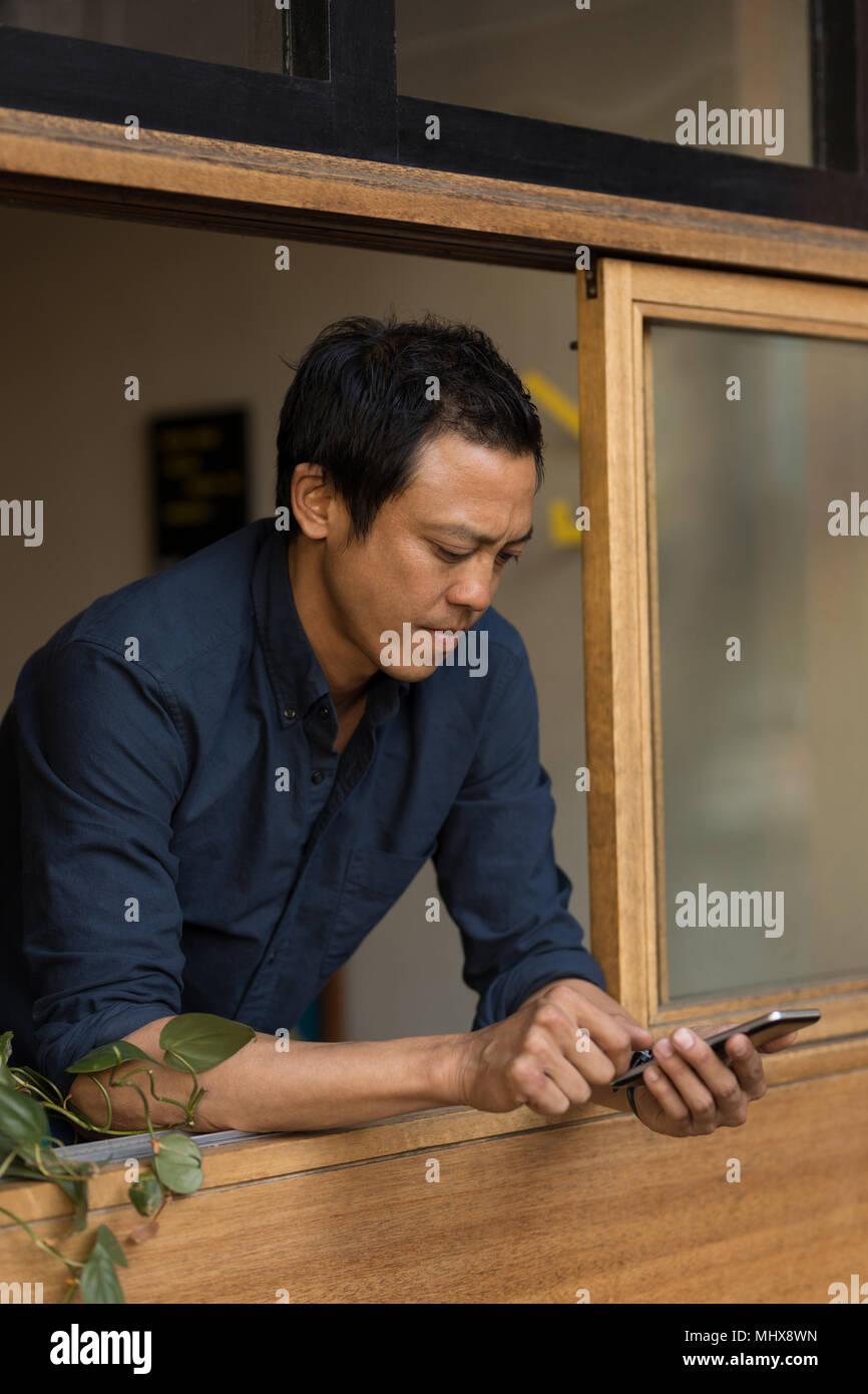 Imprenditore tramite telefono mobili in cafe Immagini Stock