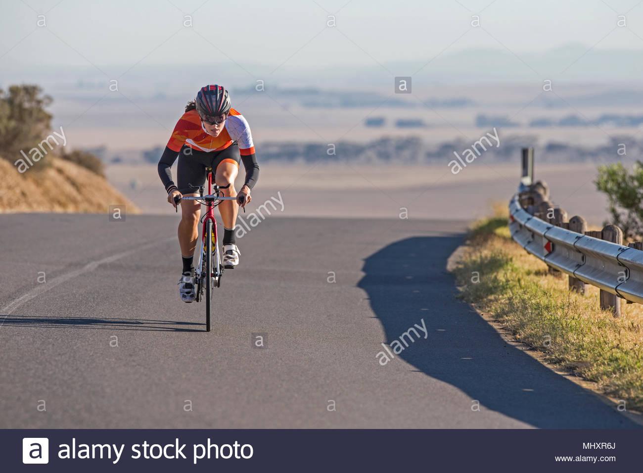 Ciclista femmina equitazione Bicicletta da corsa sulla soleggiata strada aperta Immagini Stock