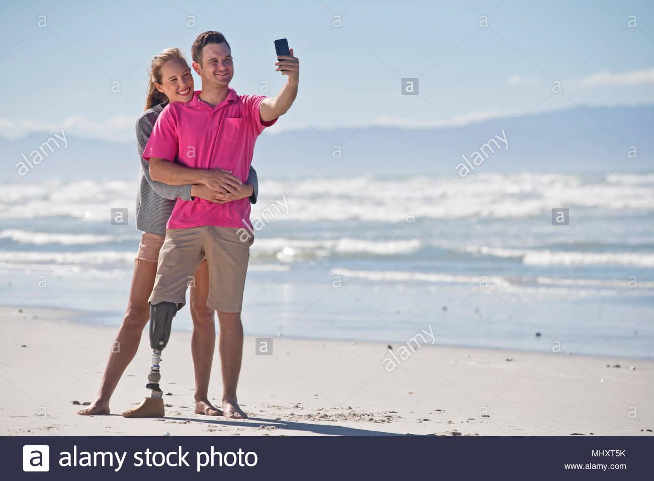 L'uomo con la gamba artificiale in posa per Selfie con partner di sesso femminile mentre in estate spiaggia vacanza in Sud Africa Immagini Stock