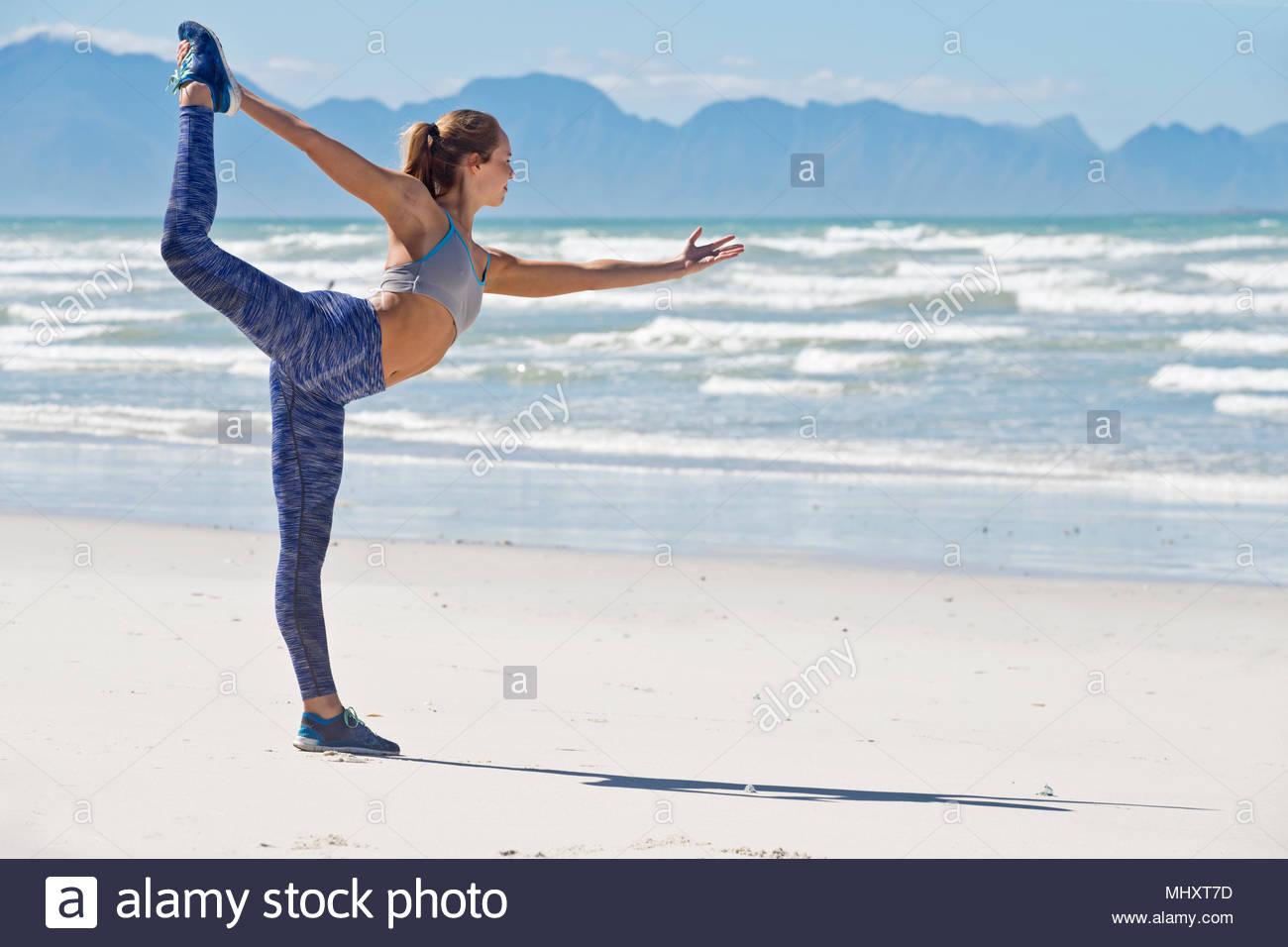 Donna in Sportswear stretching prima di esercitare sulla spiaggia in Sud Africa Immagini Stock