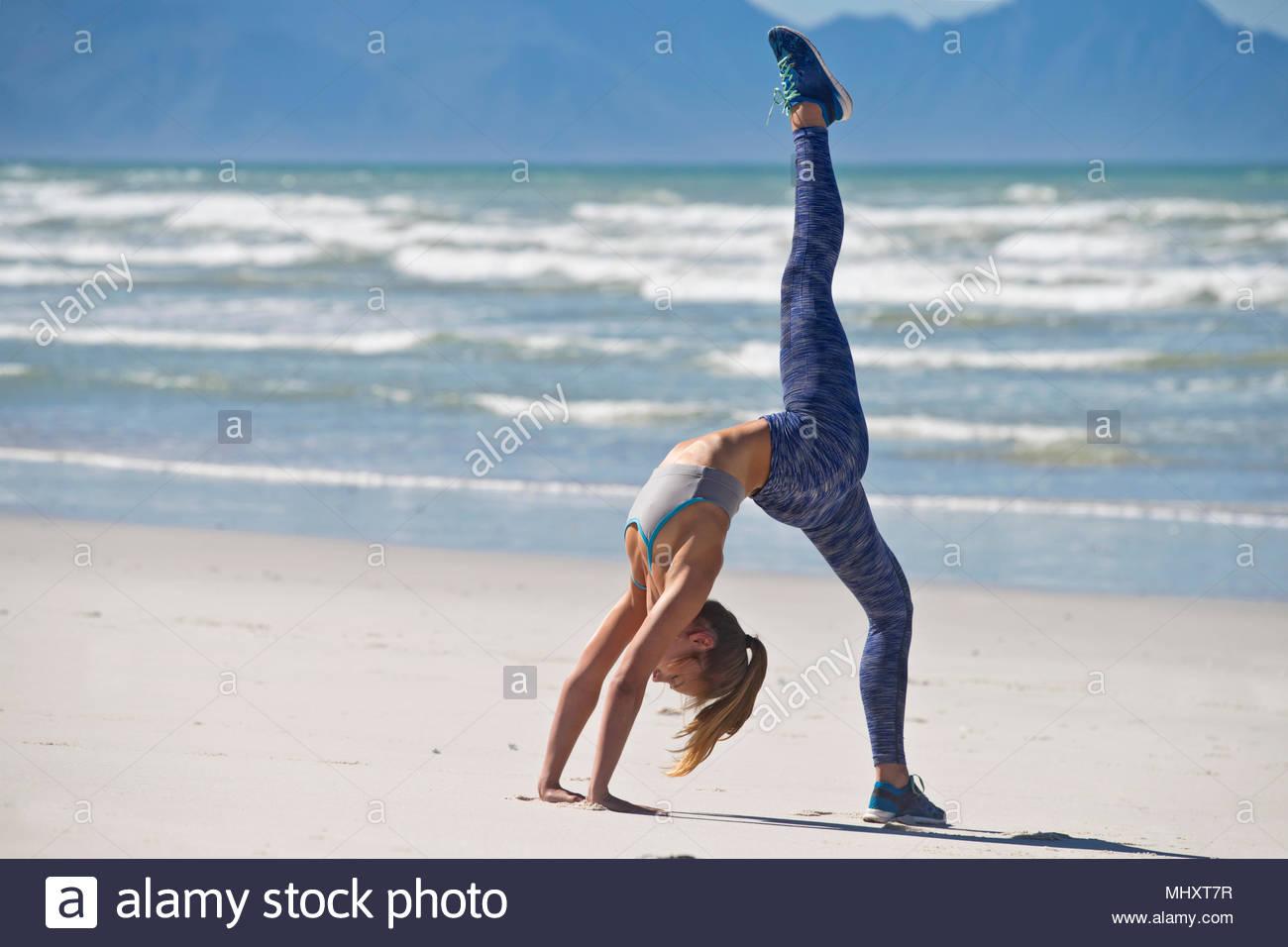 Donna che indossa abbigliamento sportivo in posa di Ginnastica sulla Spiaggia in Sud Africa Immagini Stock