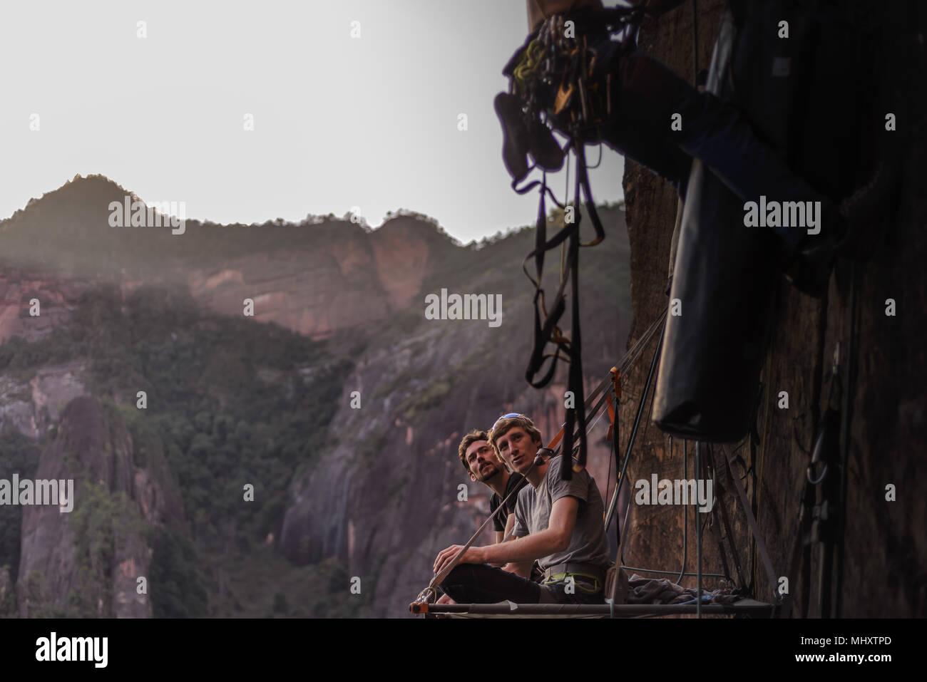 Due arrampicatori udienza del portaledge, guardando amico salire rock accanto a loro, la calcinazione, nella provincia dello Yunnan in Cina Immagini Stock