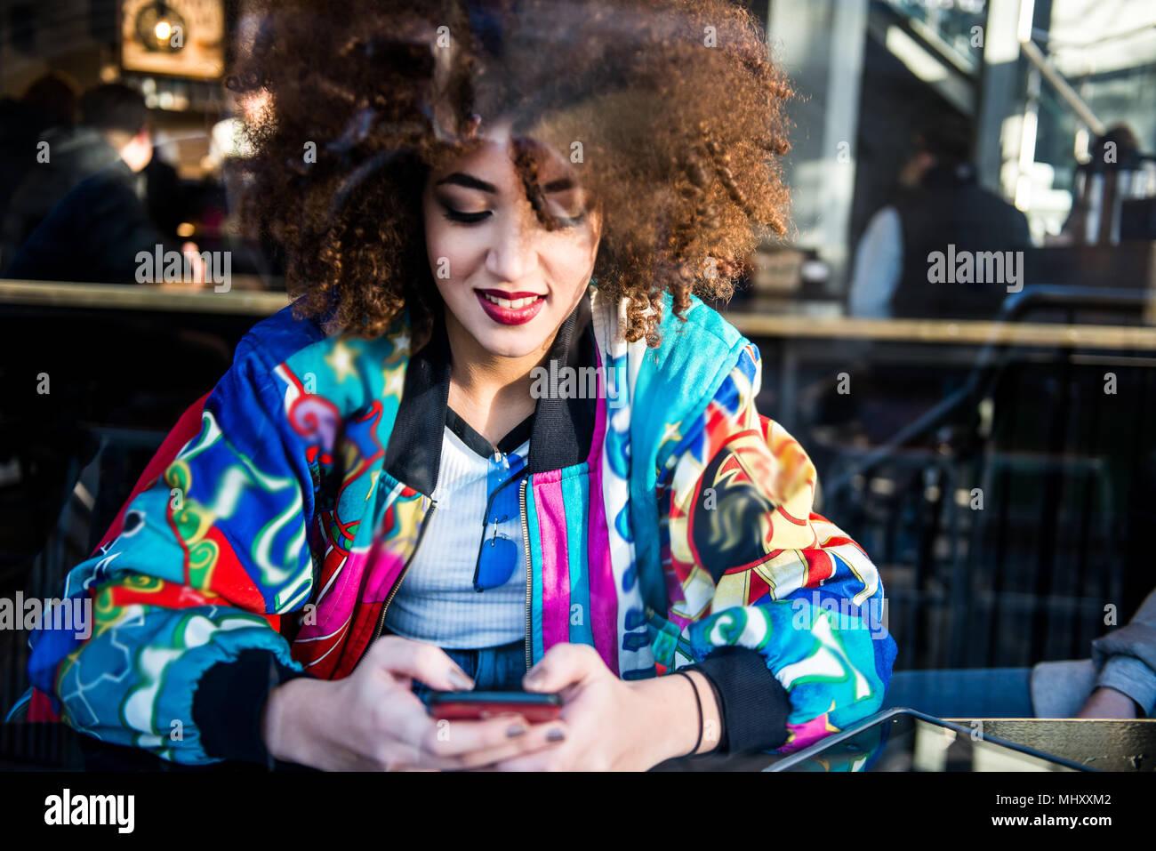 Giovane ragazza seduta nel bar, utilizza lo smartphone, vista attraverso la finestra, London, England, Regno Unito Foto Stock