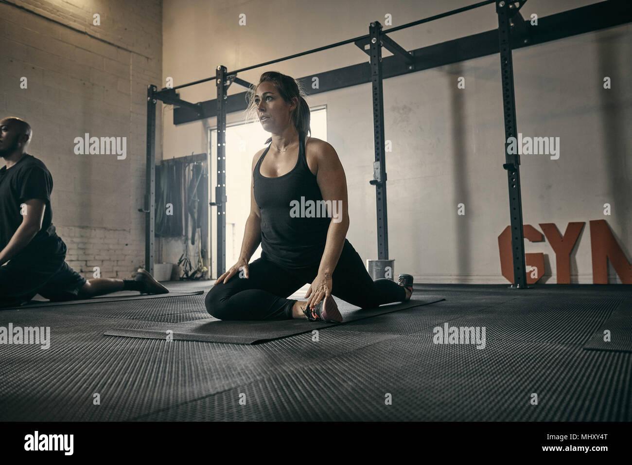 La donna in posizione di yoga in palestra Immagini Stock