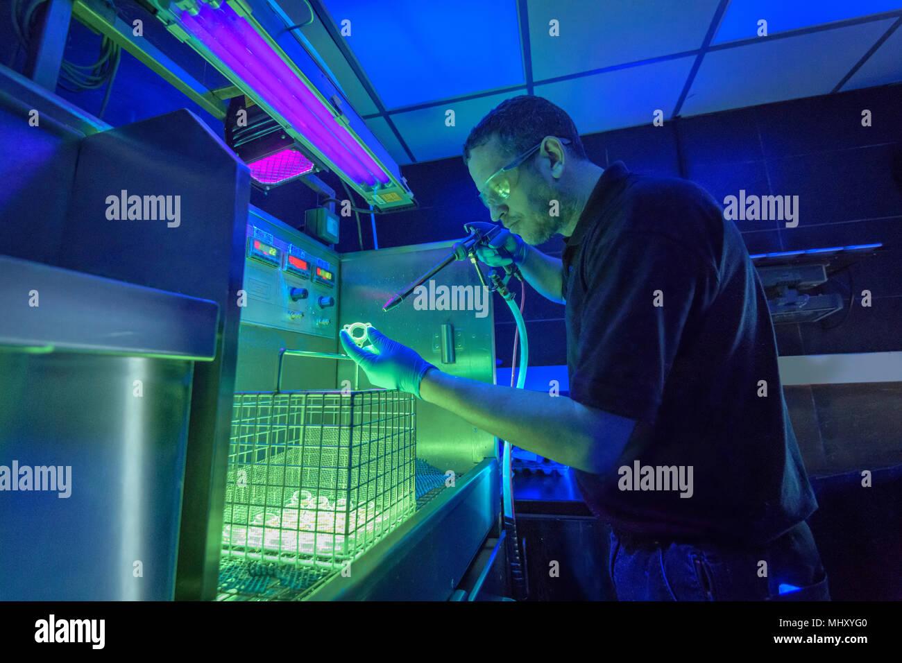 Lavoratore usando luce ultravioletta per rilevare incrinature nella fabbrica di elettroplaccatura Immagini Stock