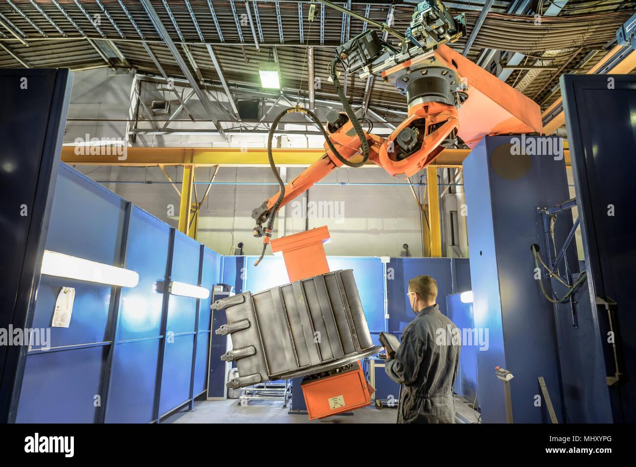 Ingegnere con robot saldatore nella fabbrica di ingegneria Immagini Stock