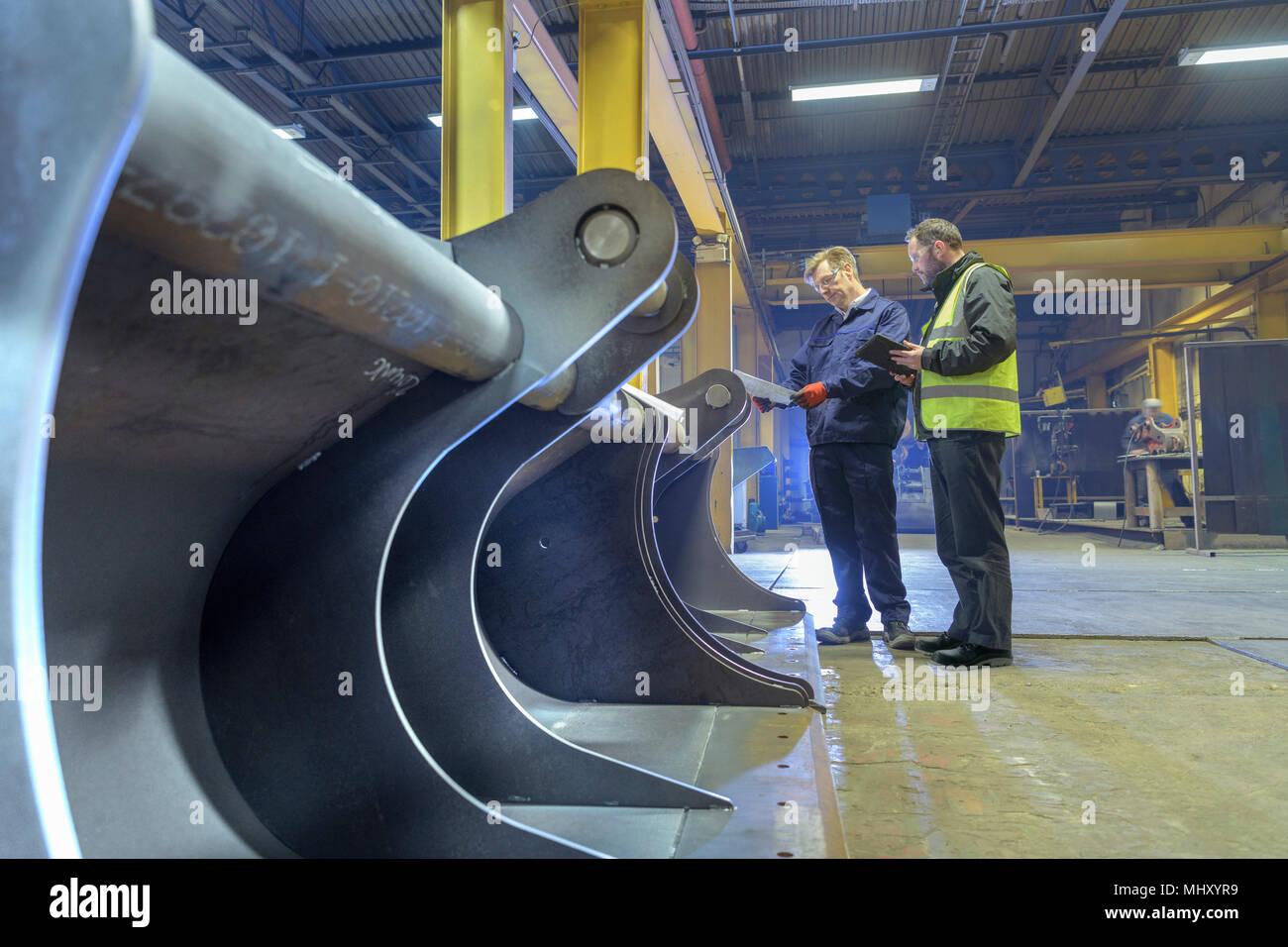 Il lavoratore e il manager di ispezionare in parte prodotto finito nella fabbrica di ingegneria Immagini Stock