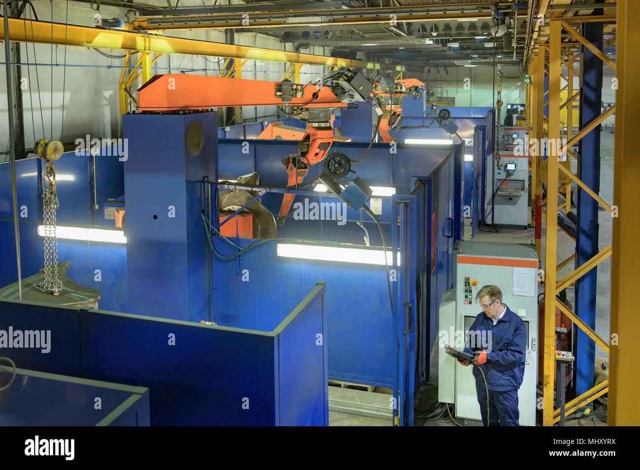 Angolo di alta vista del robot saldatore nella fabbrica di ingegneria Immagini Stock