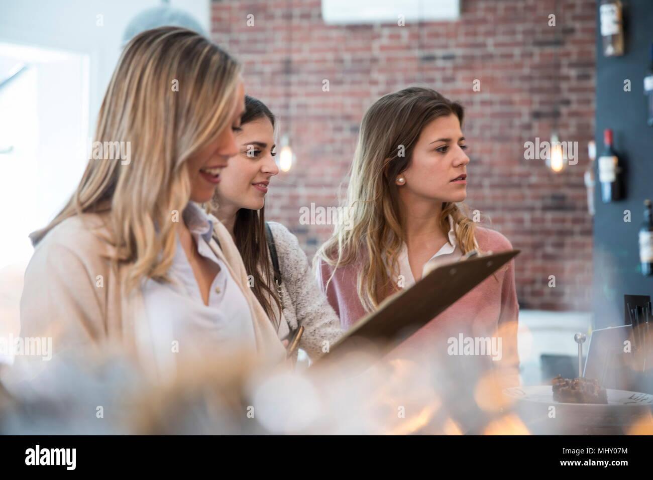 Tre amici di sesso femminile, permanente al contatore in cafe Immagini Stock