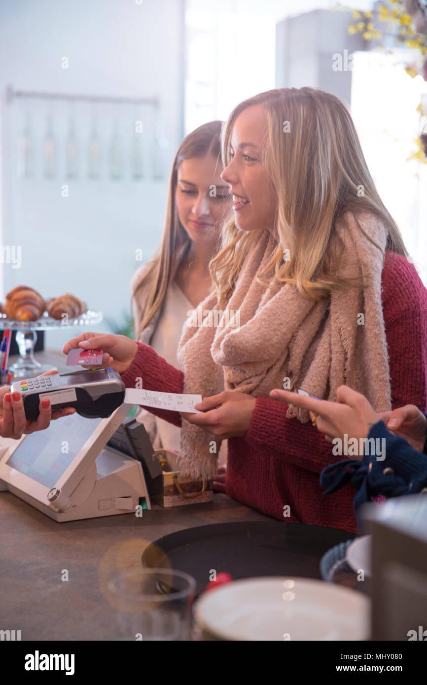 Amici di sesso femminile permanente al contatore in cafe, pagando con carta di credito Immagini Stock