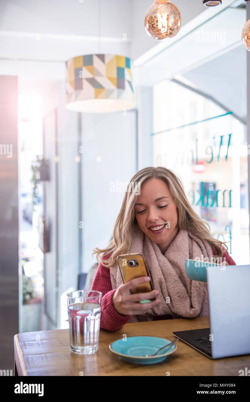 Donna seduta al cafe, guardando smartphone, tenendo tazza da caffè Immagini Stock