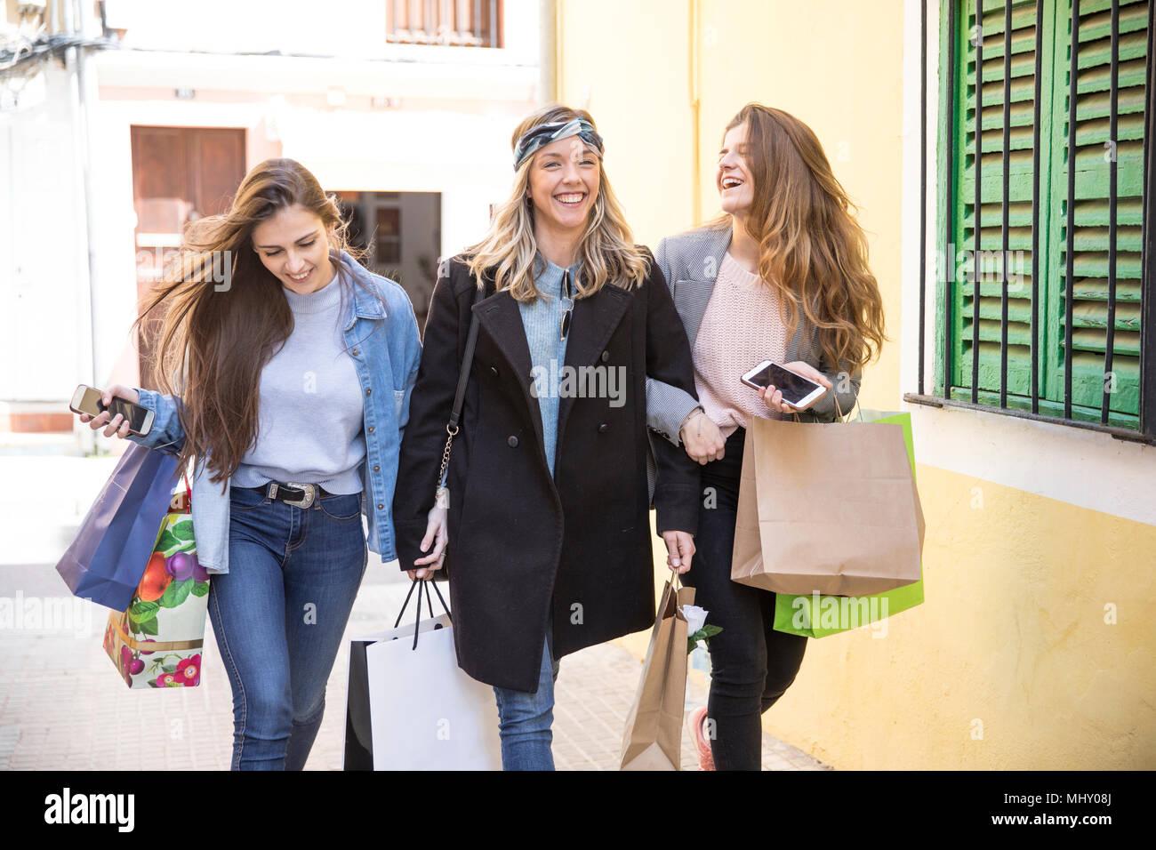 Gli amici di shopping e ridere in strada Immagini Stock