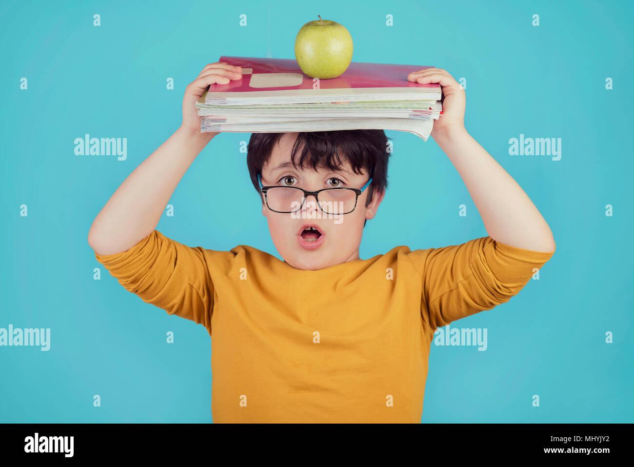 Ragazzo sorpreso con libri e Apple su sfondo blu Immagini Stock
