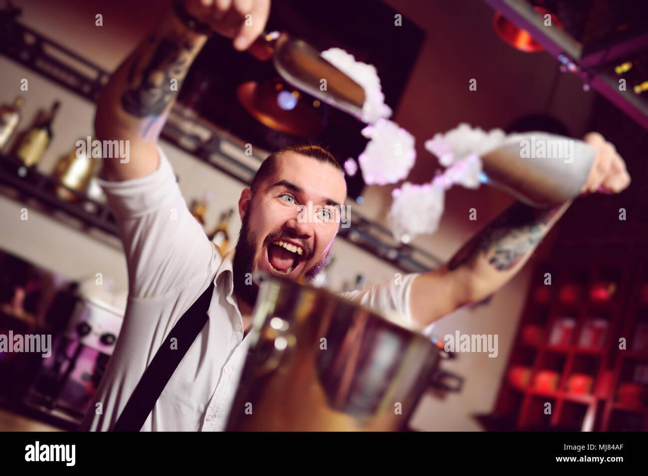 Allegro barman sorrisi, urla e si addormenta in un secchiello per champagne sullo sfondo della barra. Immagini Stock