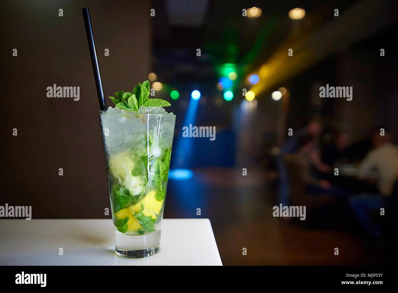 Ice cocktail mojito decorate con un rametto di menta e paglia di nero su un banco di bar vicino. Immagini Stock