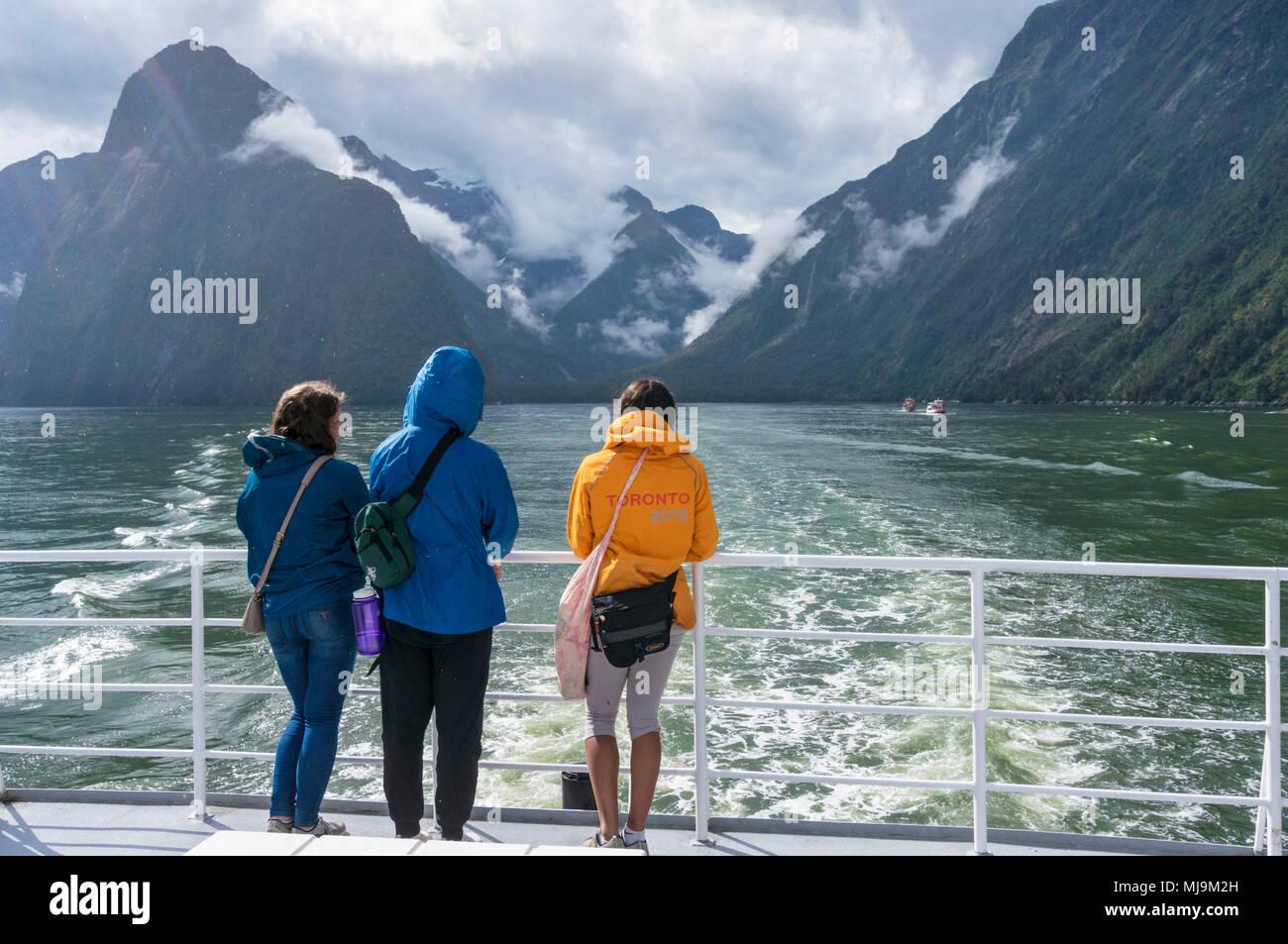 Milford Sound Nuova Zelanda Milford Sound tre amici si fermò a prua di una barca per gite di ritorno da un viaggio in barca sul Milford Sound Isola del Sud Foto Stock