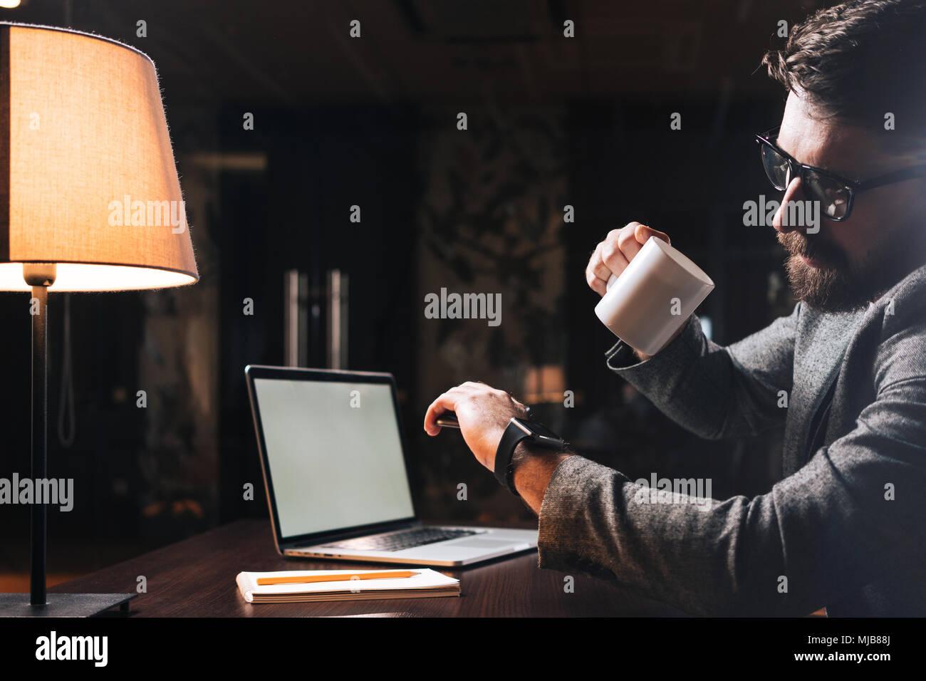 Giovane imprenditore barbuto contiene una tazza di tè e guardare su smartwatch sulla sua mano. Collaboratore del processo di lavoro di notte office Immagini Stock