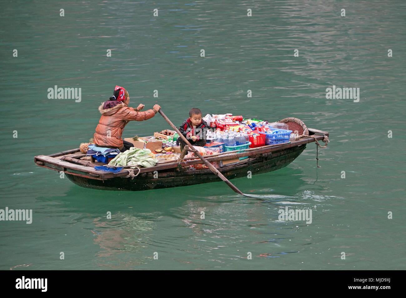 Una barca piena di lavoratori di sesso femminile indossando cappelli di  bambù nella baia di Halong d70811b00305