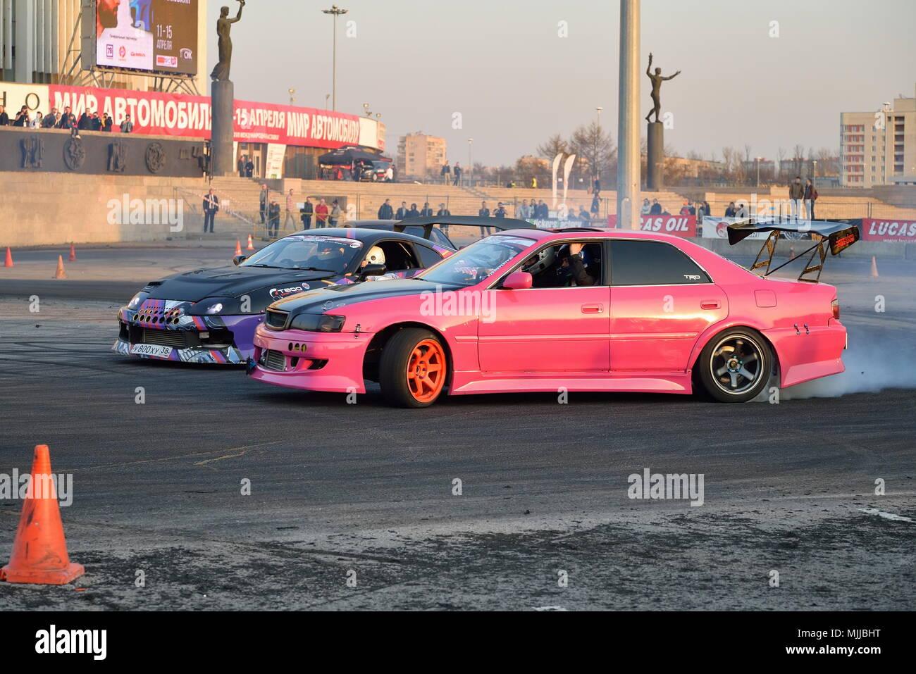 Rosa auto racing concorrenti sulla via T800 con un auto vicino alla Immagini Stock
