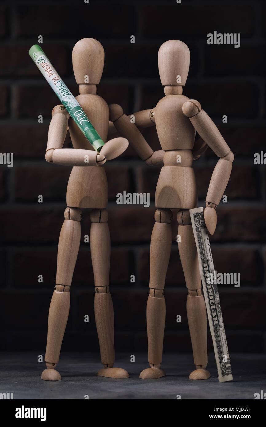 Due figure della persona fatta di un albero a uno in mani di rubli russi e a un altro il dollaro americano, simboleggiano l'amicizia. Immagini Stock
