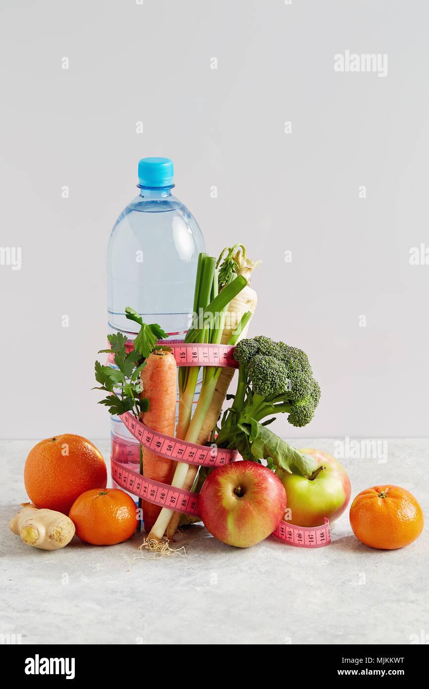 Bottiglia di acqua con una rosa di nastro di misurazione, la frutta e la verdura. Concetto la salute, la dieta e la nutrizione. Immagini Stock