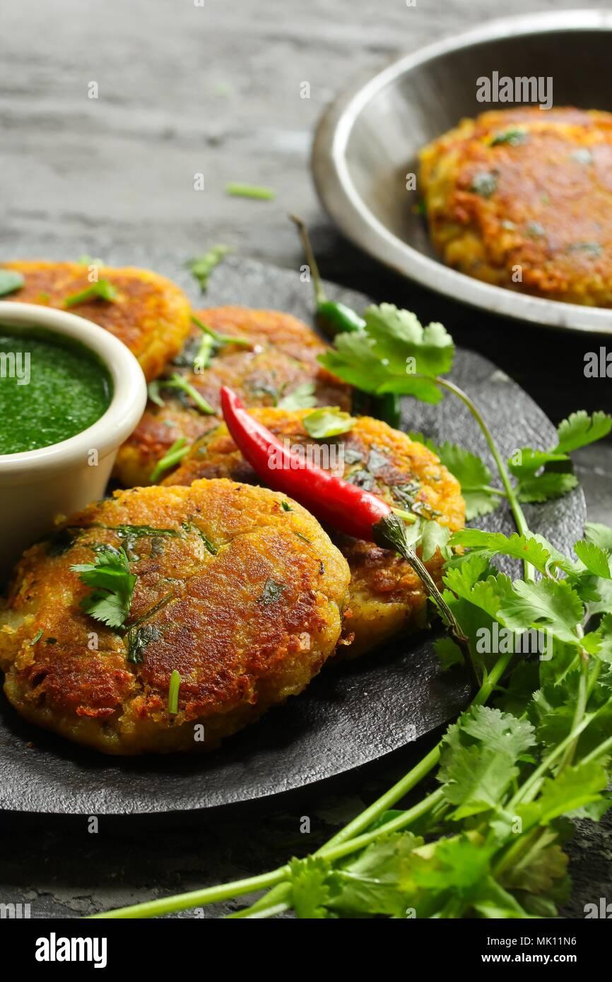 , Aloo Tikki / Indian snack polpette di patate servita con chutney di coriandolo Immagini Stock