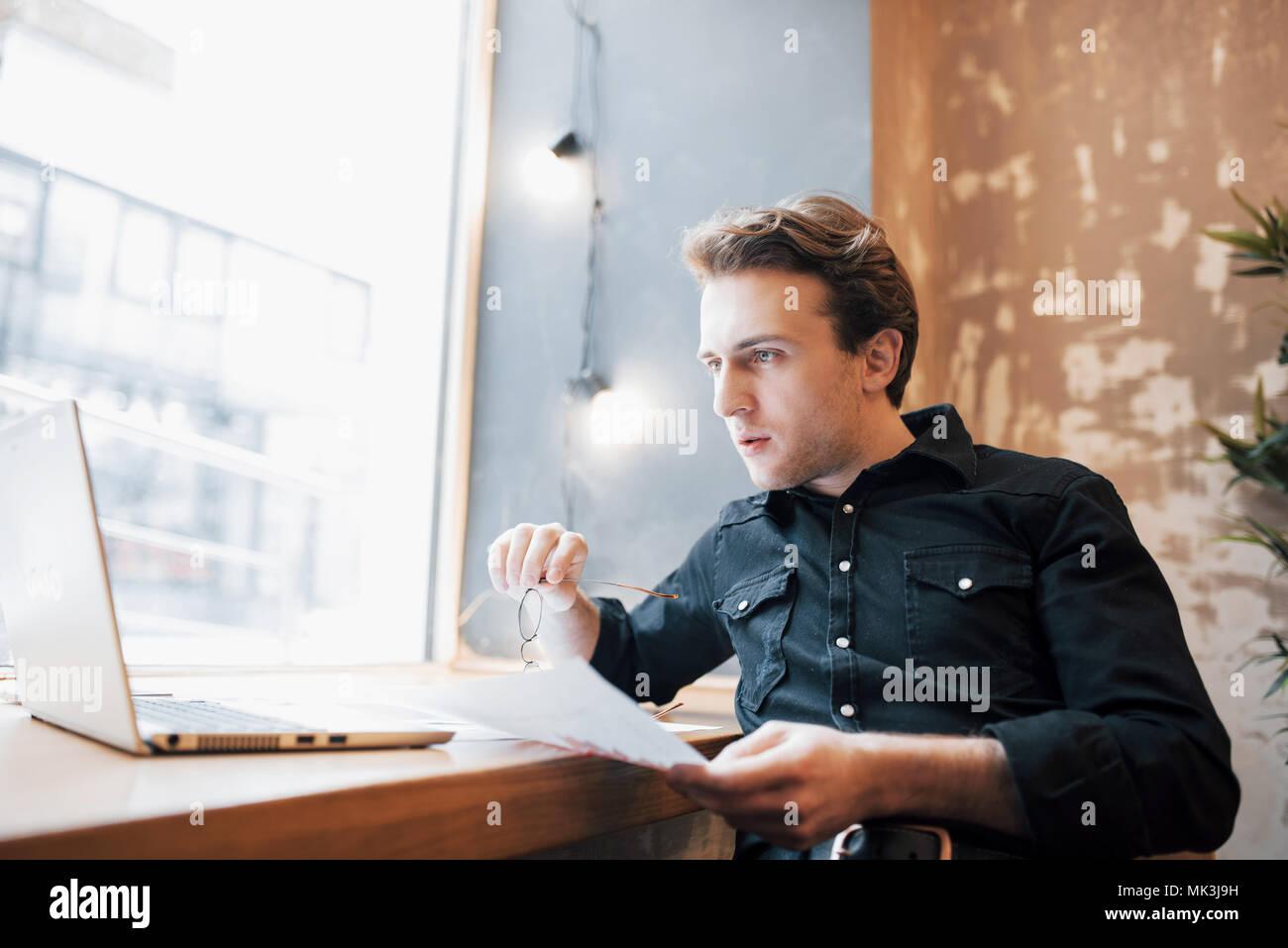 Rilassata giovani professionisti la navigazione in Internet sul suo computer portatile in un cafe Immagini Stock