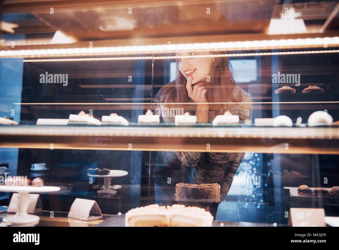 Donna sorridente alla telecamera attraverso la vetrina con dolci e torte in moderno Cafe interior Immagini Stock
