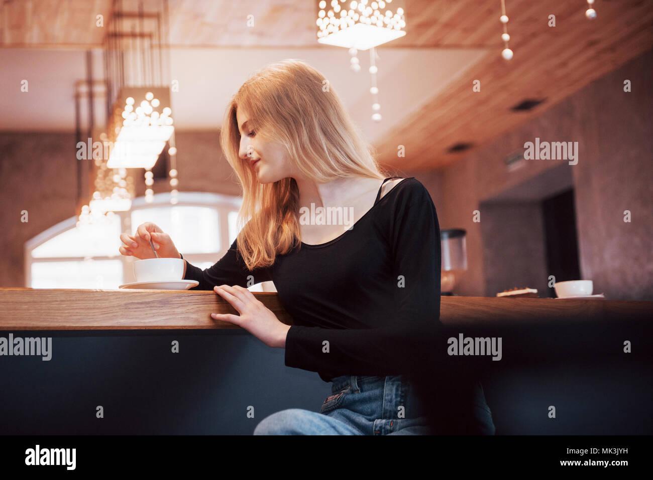 Donna sorridente al cafe' utilizzando il telefono cellulare e sms in reti sociali, seduto da solo Immagini Stock