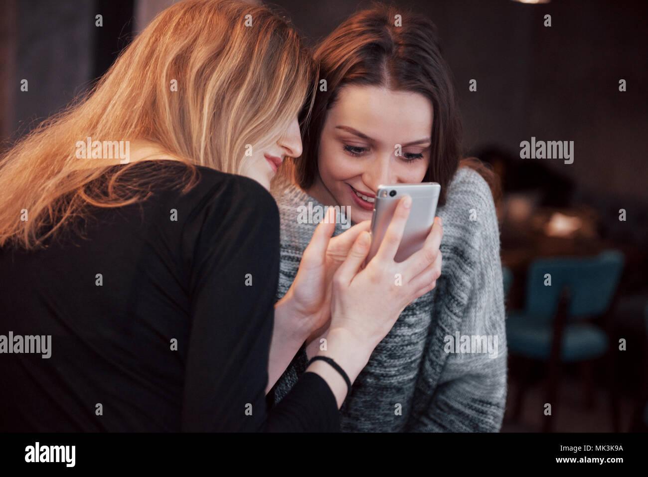 Due amici sorridenti lettura divertente la chat online su telefono moderno seduta con gustosi caffè nel ristorante.Hipster ragazze godendo di tempo libero nel bar con bevande calde e messaggistica su cellular Immagini Stock